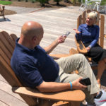 man and woman sitting on Adirondack chairs taking on a sundeck