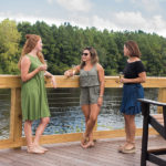 three women standing on the deck holding a beverage